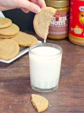 cookie being dipped into milk with plate of cookies in background