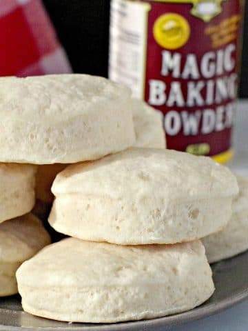 baking powder biscuits piled on a plate with magic baking powder in background
