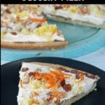 slice on Carrot Cake Dessert Pizza on a black plate with pizza in the background