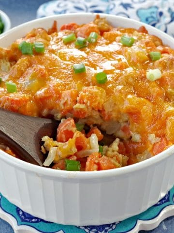 carrot casserole in white casserole dish with a brown wooden spoon scooping casserole (on blue background) with dish of green onions and oven mitts in the background