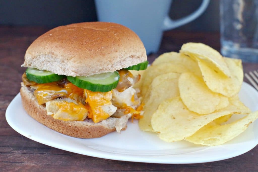 diced chicken breast burger on white plate with side of potato chips