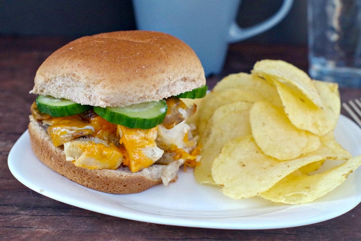 chicken breast burger on a white plate with potato chip and blue coffee mug in the background