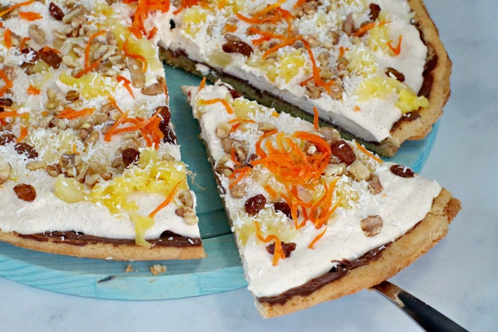 carrot cake dessert pizza slice being removed from pizza