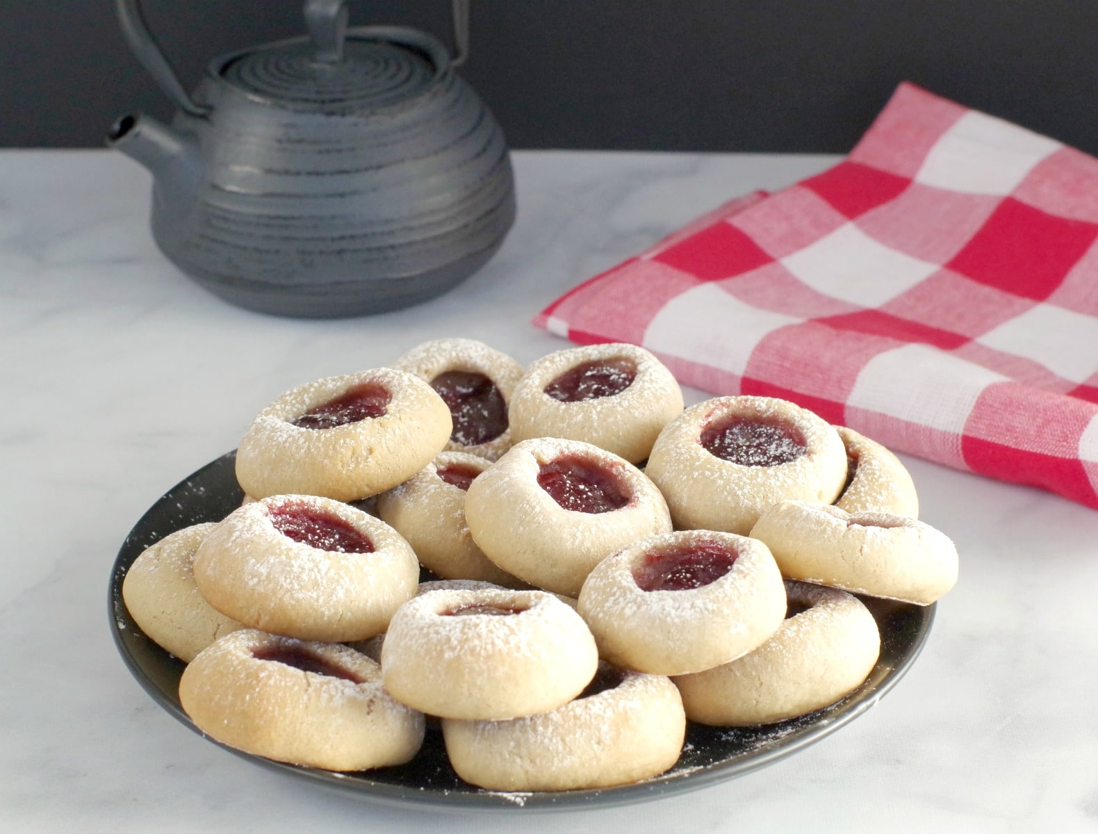 raspberry jam thumbprint cookies on a black plate with black tea pot and red checkered tea towel in the background