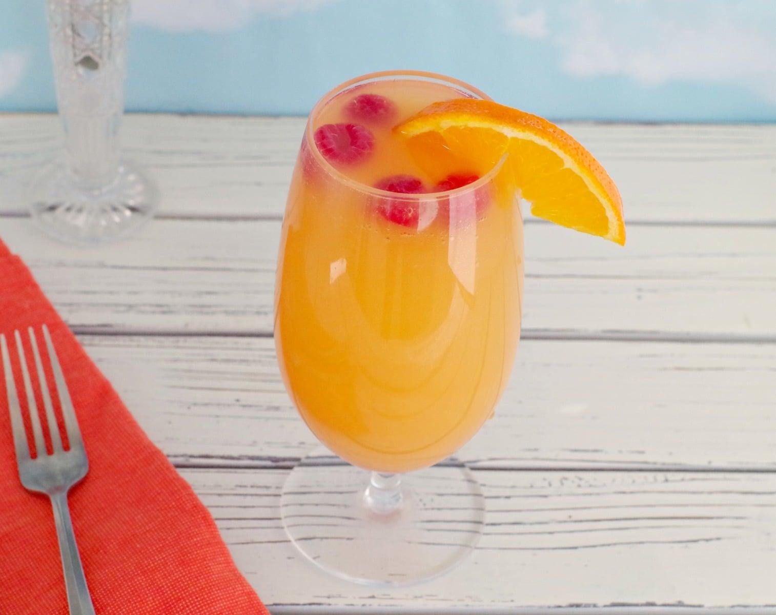mimosa drink with raspberries and orange garnish