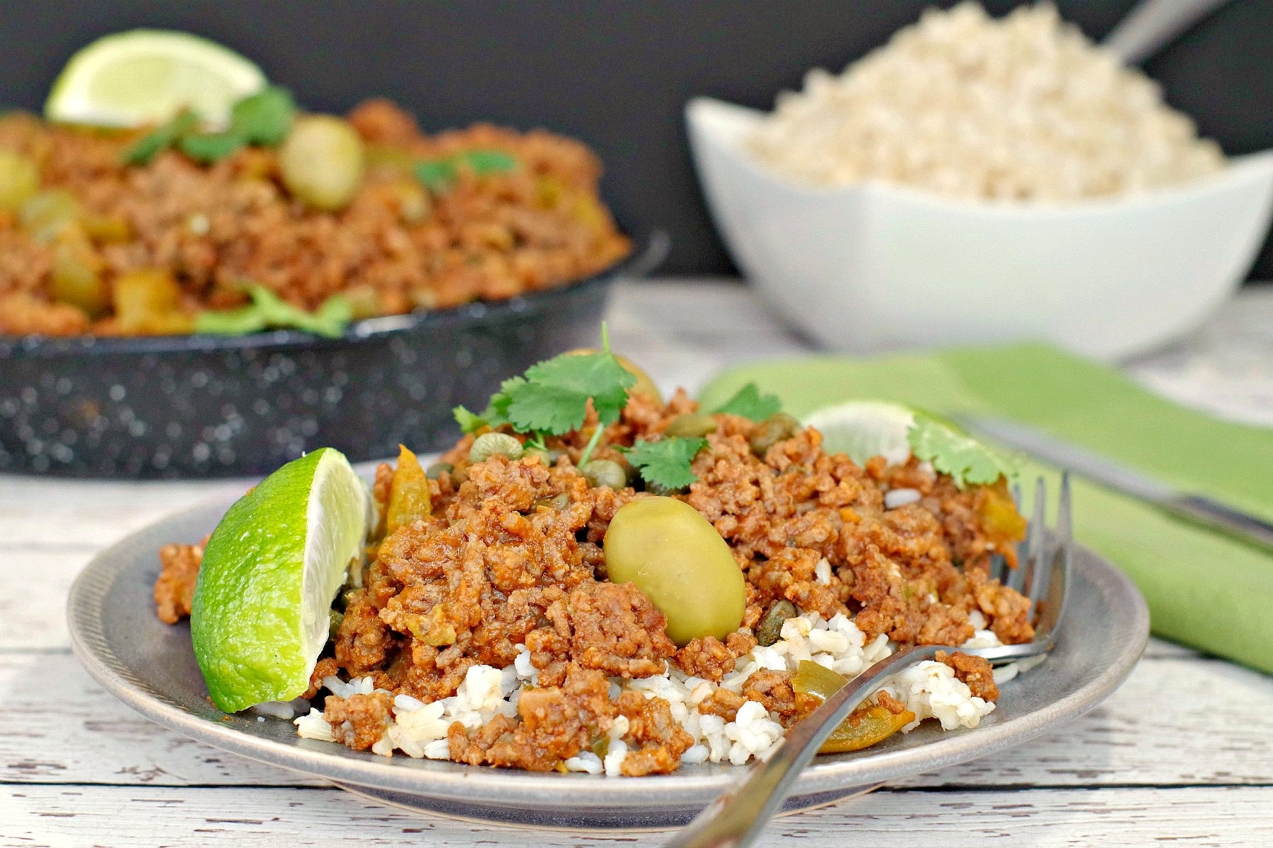 Picadillo over rice with rice and pan of picadillo in background
