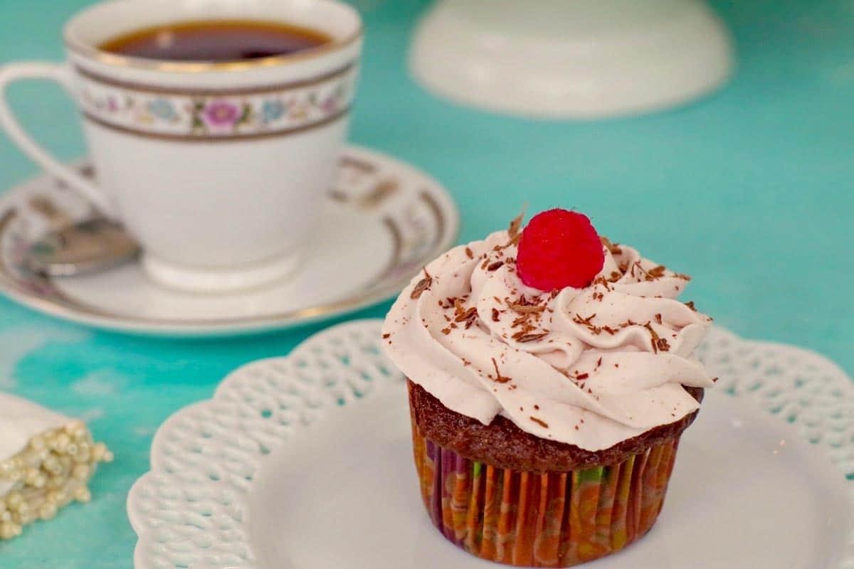 tiramisu cupcake on a white plate, with a cup of tea (in a china cup) in the background