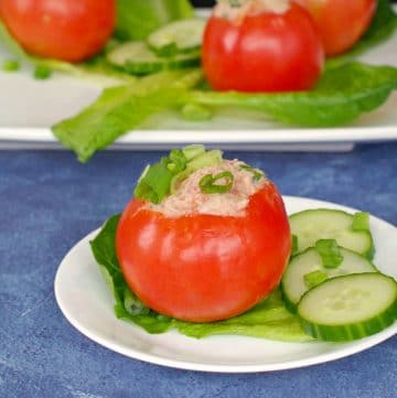 Tuna stuffed tomato on white plate with 3 more tomatoes on platter in background