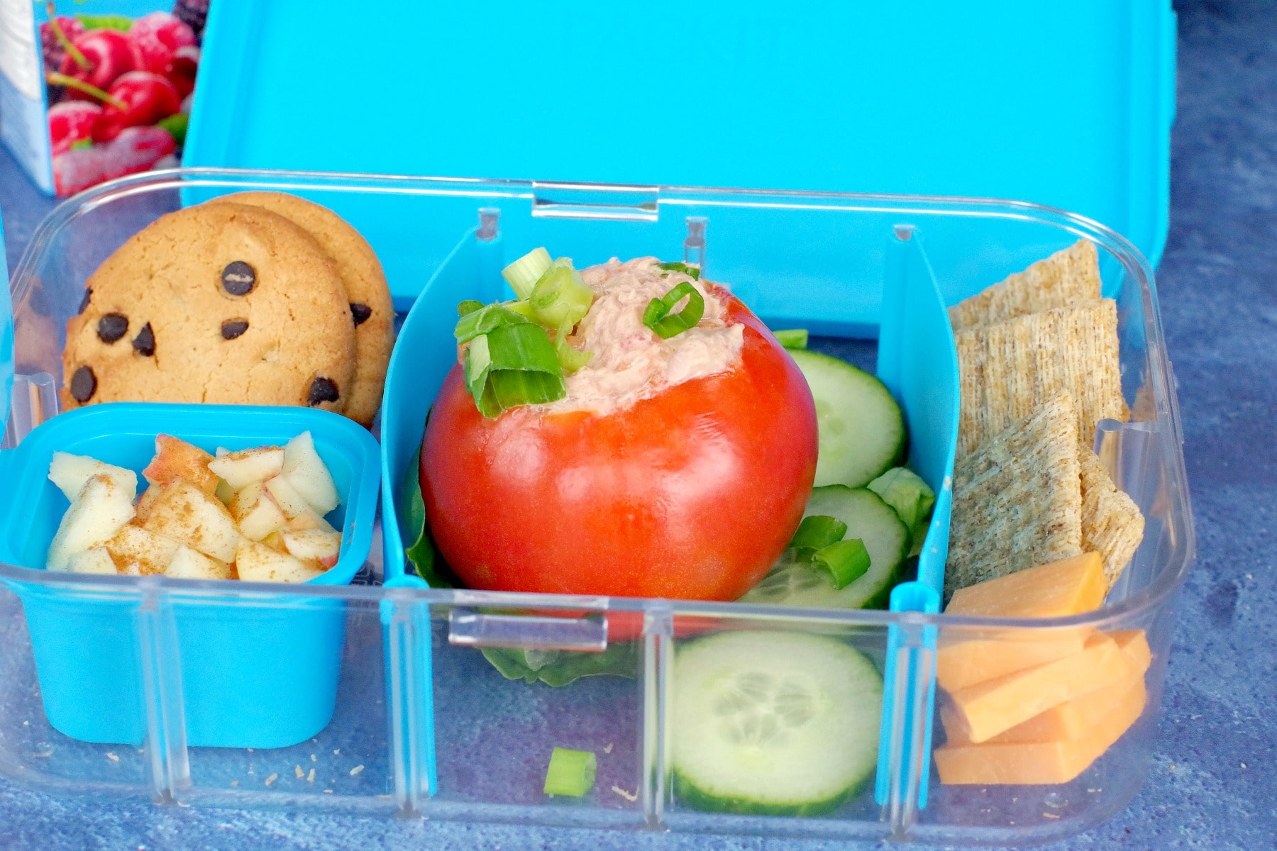 stuffed tomatoes in lunch box with cracker, cheese, cookies and apple yogurt