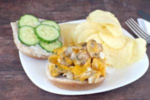 chicken breast sandwich on plate with chicken and mushrooms on one side and cucumber on other side of bun