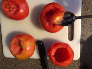insides being scooped out of tomato