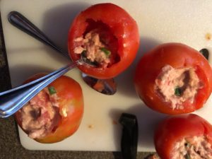 mixture being stuffed back into tomatoes