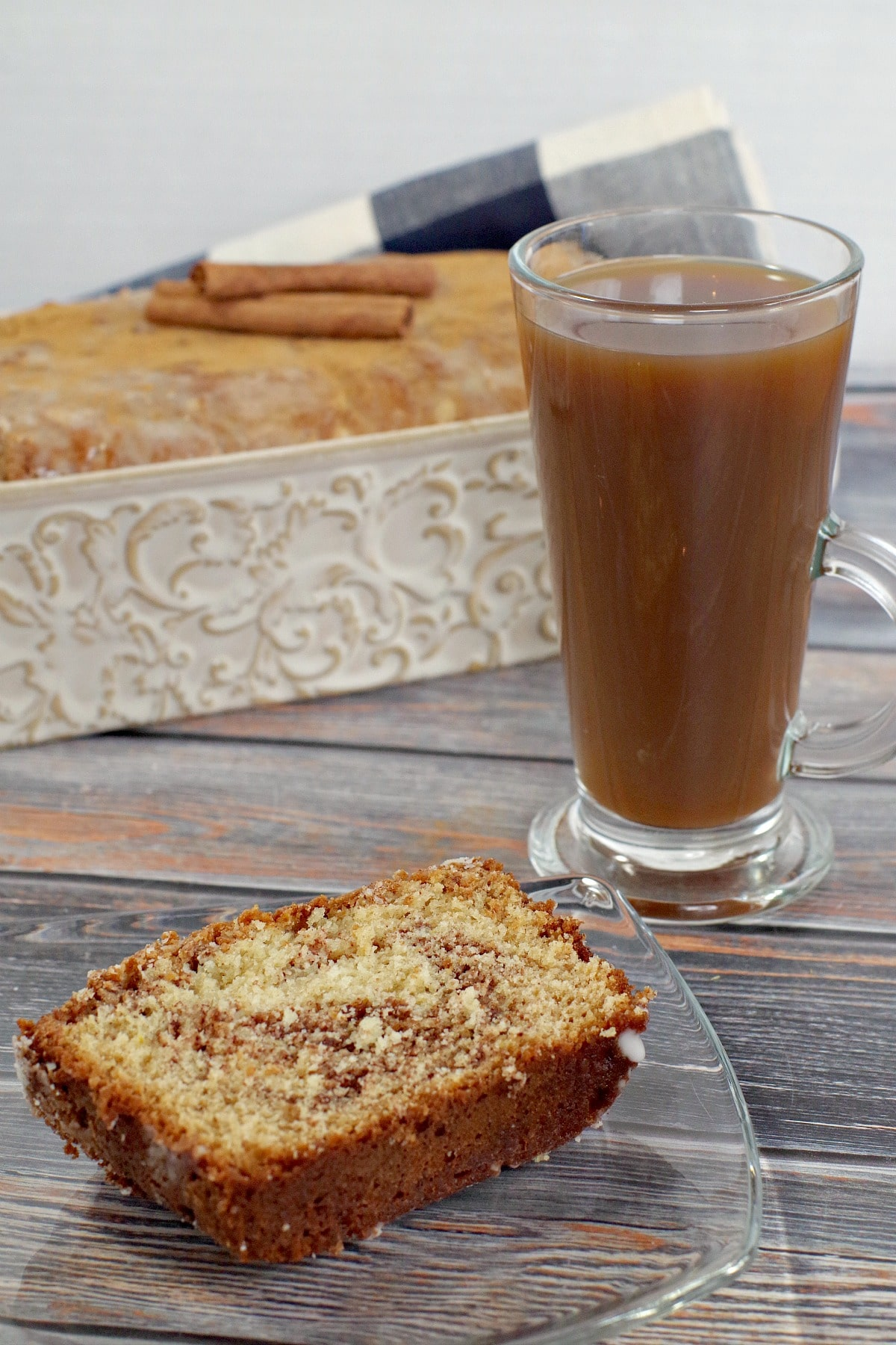 slice of cinnamon bread on a glass plate next to a cup of coffee and loaf pan in background