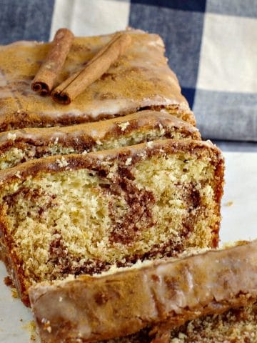 cinnamon loaf on marble cutting board with blue and white checkered tea towel in background