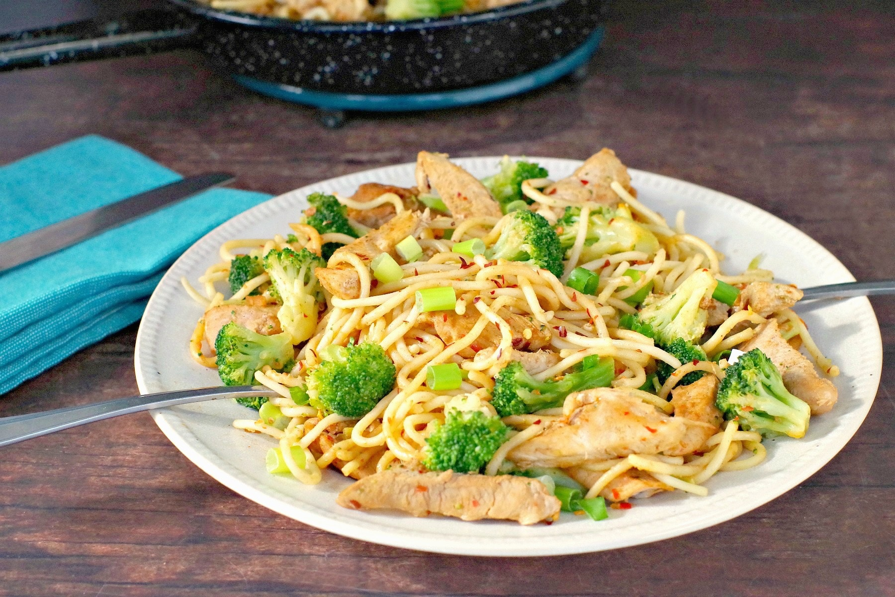 easy thai pork noodles on white plate on brown surface