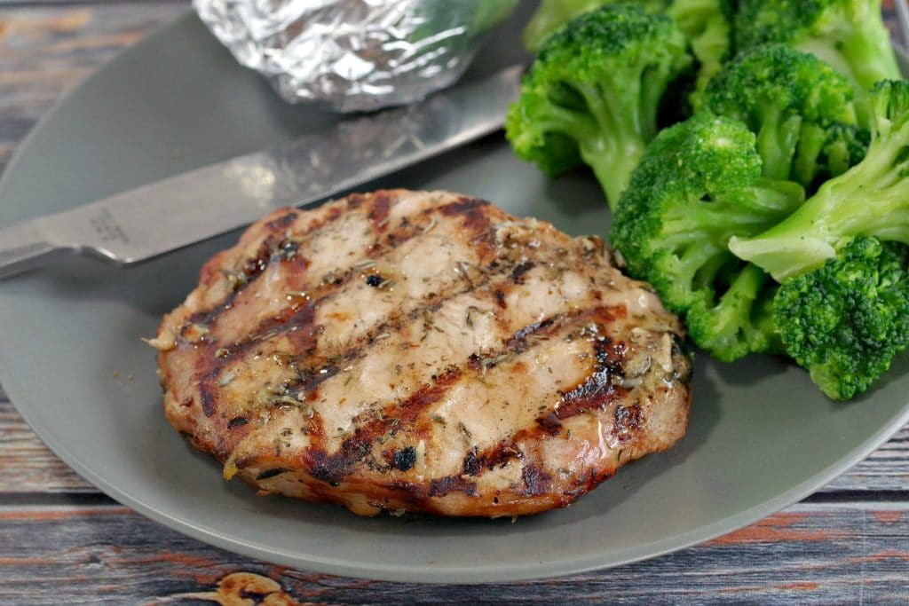 Maple lemon pork on a plate with broccoli and baked potato in foil