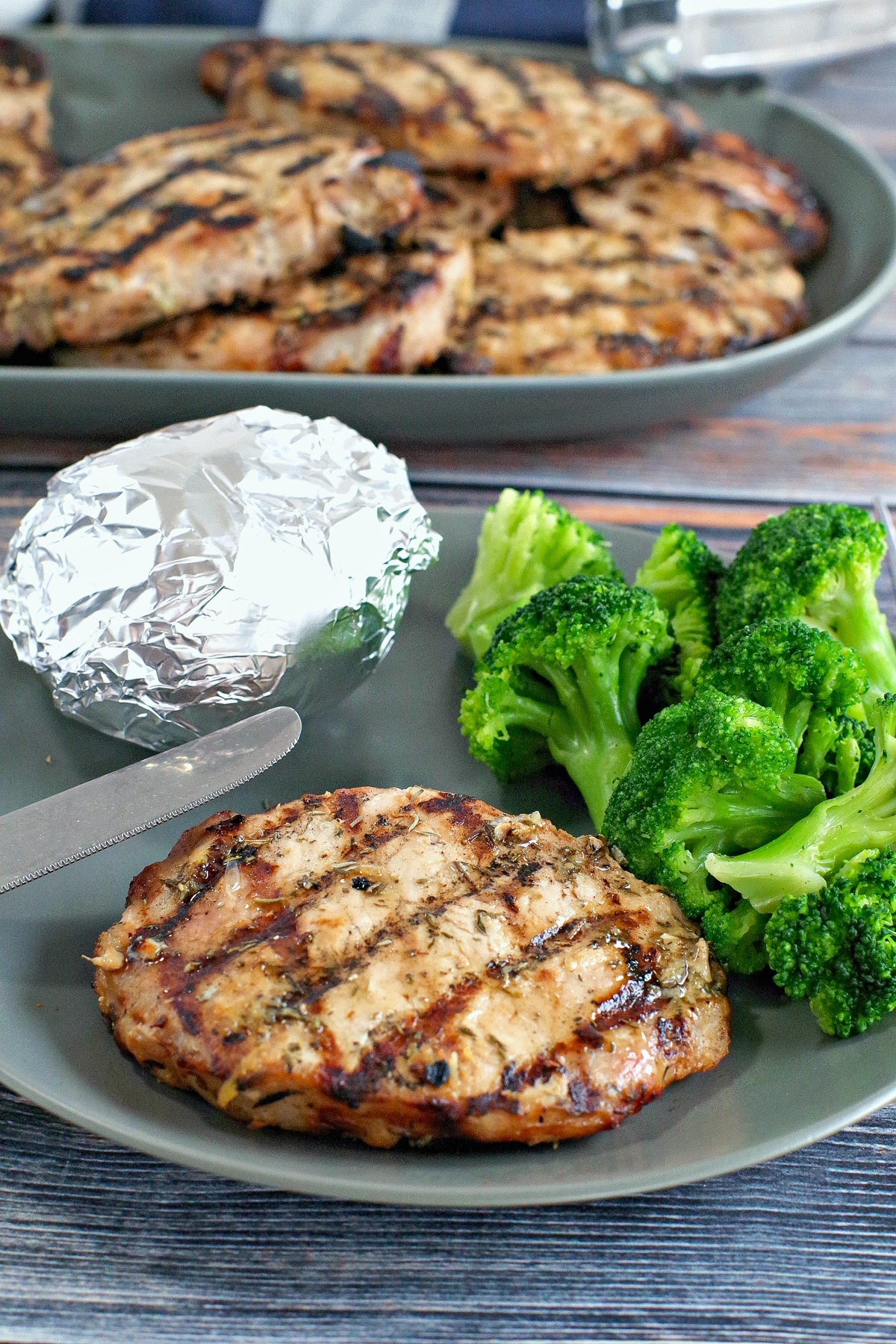 Maple lemon pork on a plate with broccoli and baked potato in foil with platter of pork in the backgroun