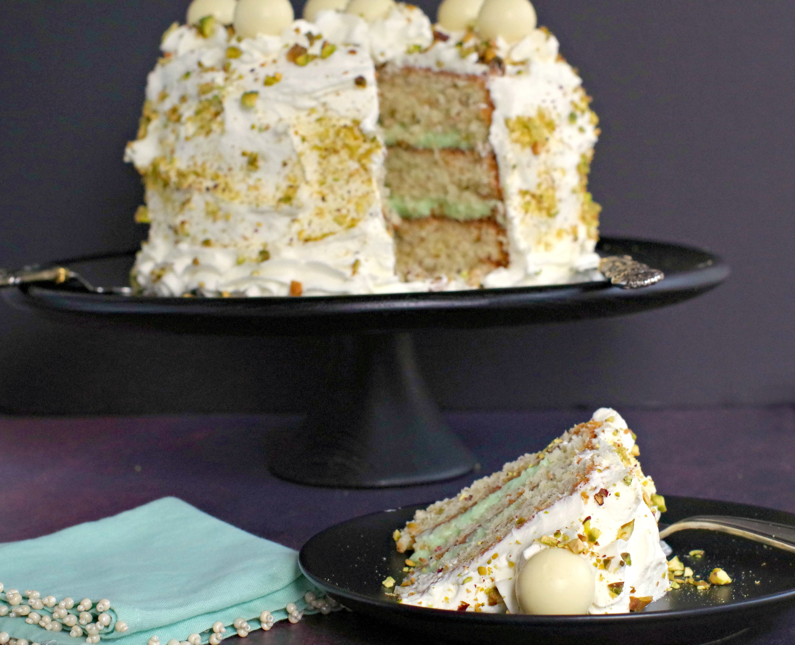 Pistachio White Chocolate Cake on black tray in background with piece of cake in the front