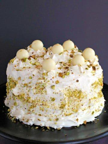 White Chocolate Pistachio cake on black stand