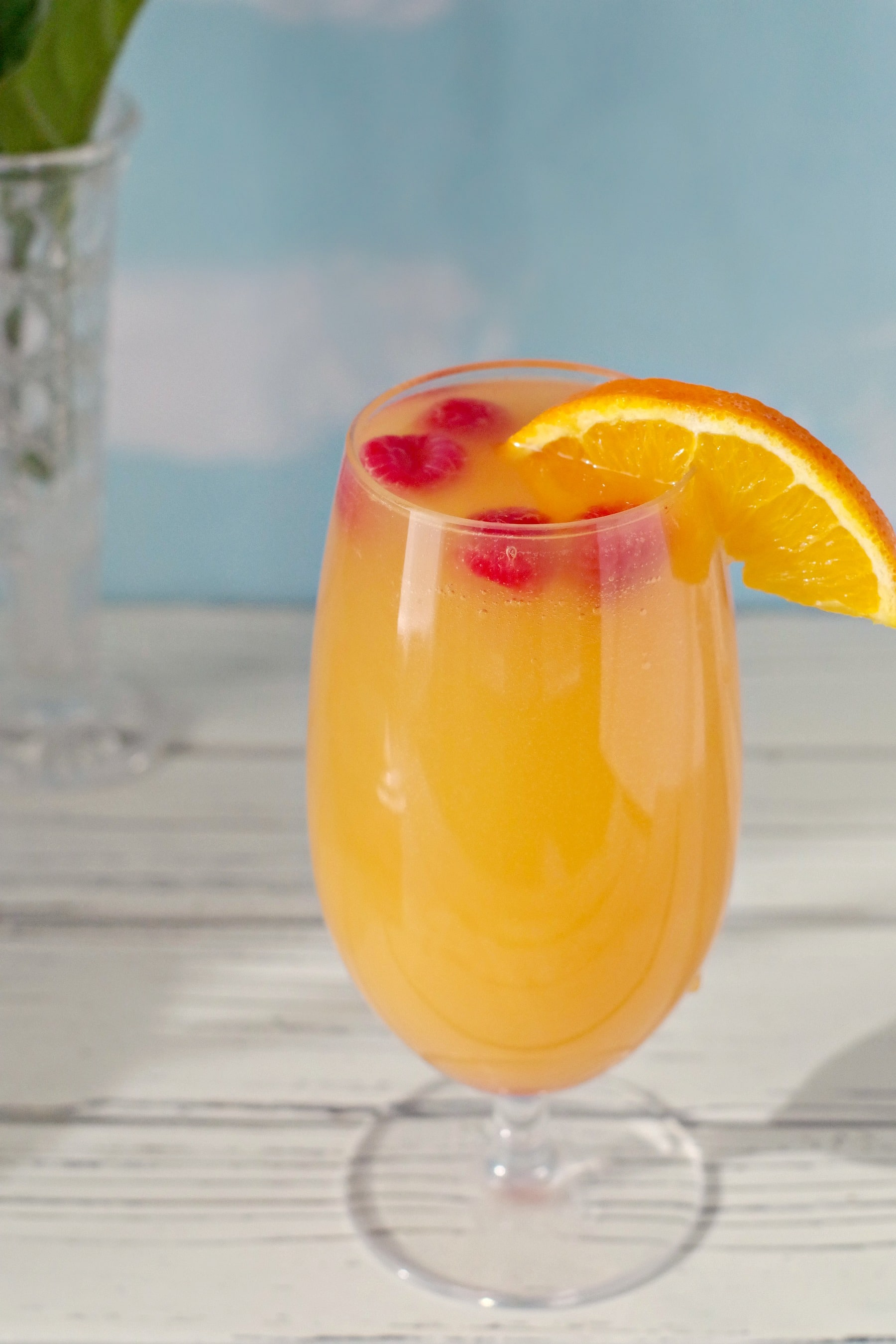 mimosa drink with raspberries and orange garnish