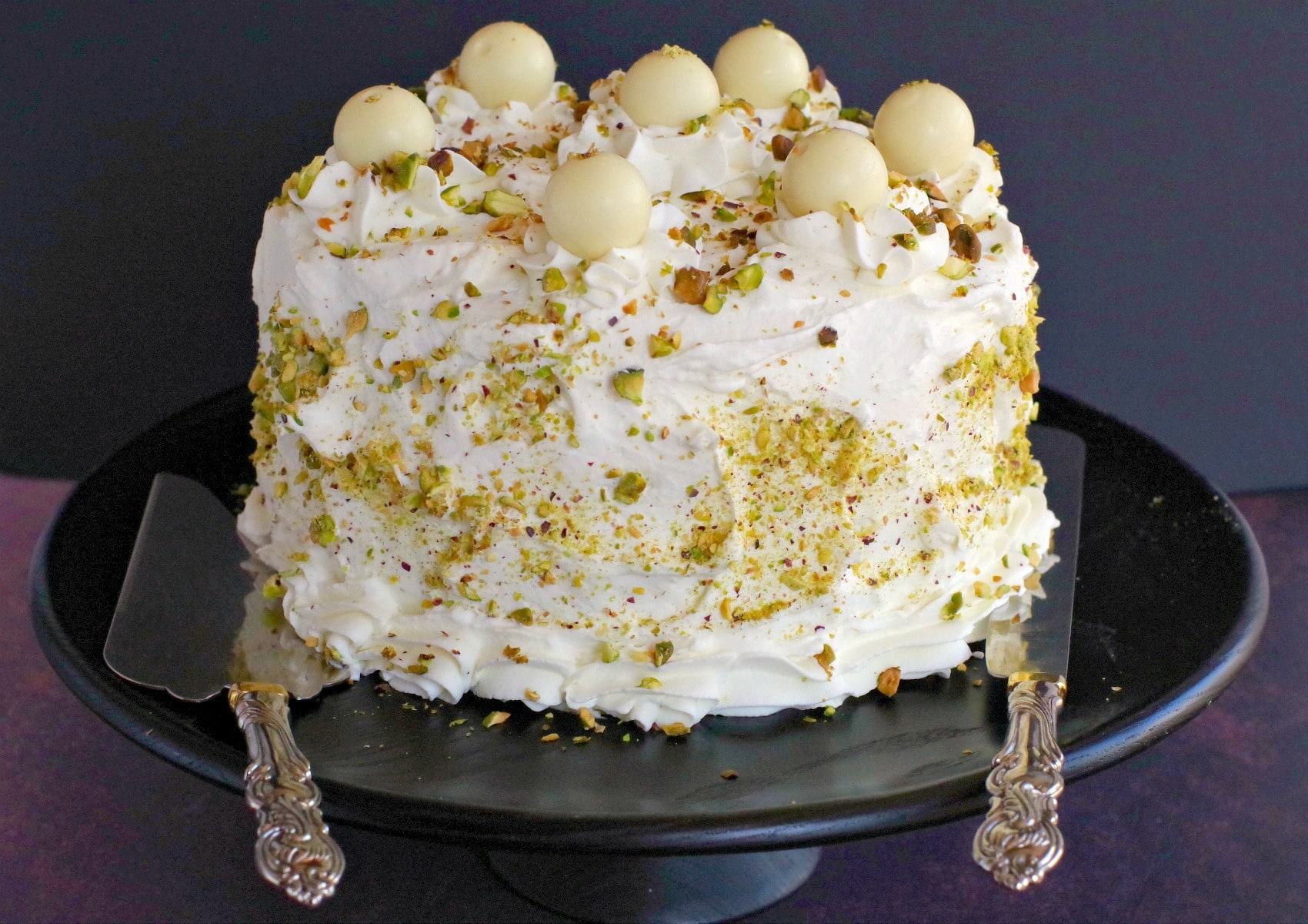 Pistachio Cake on black stand with cake lifter and knife resting on each side