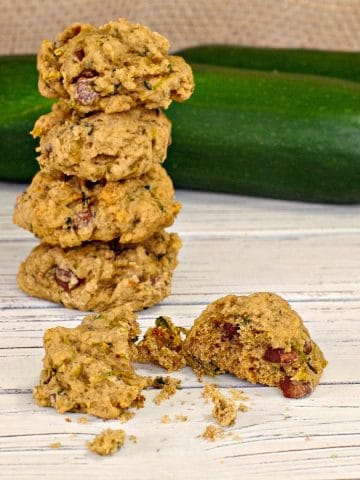 zucchini chocolate chip cookies stacked in back with one broken on in front
