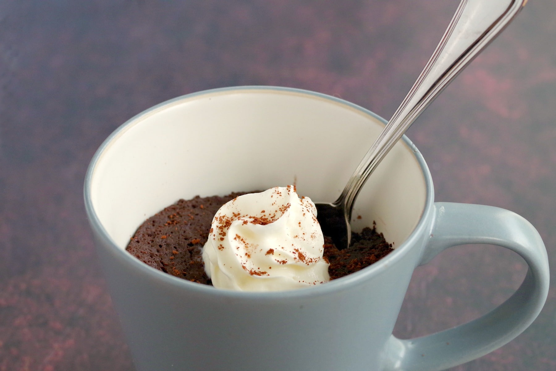 microwave chocolate banana mug cake with a spoon in it