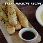 4 Italian breadsticks (bread machine recipe) on a wooden cutting board with a dish of balsamic vinegar on the end of the cutting board
