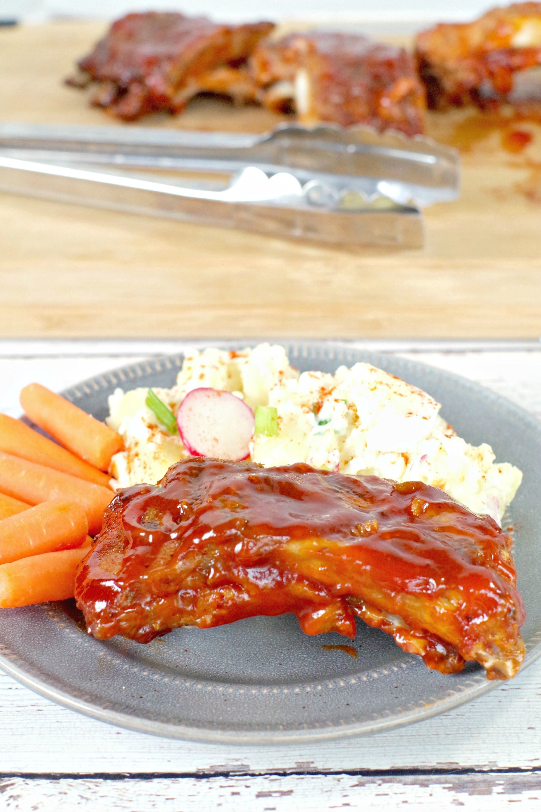 slow cooker BBQ beer ribs on a plate with potato salad and carrots