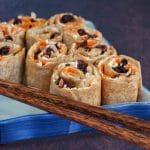 tortilla pinwheels on a blue sushi platter with chopsticks