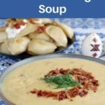 Pin with white text on blue background (on top and bottom) and photo of pierogi soup in the middle, with plate of perogies in the background