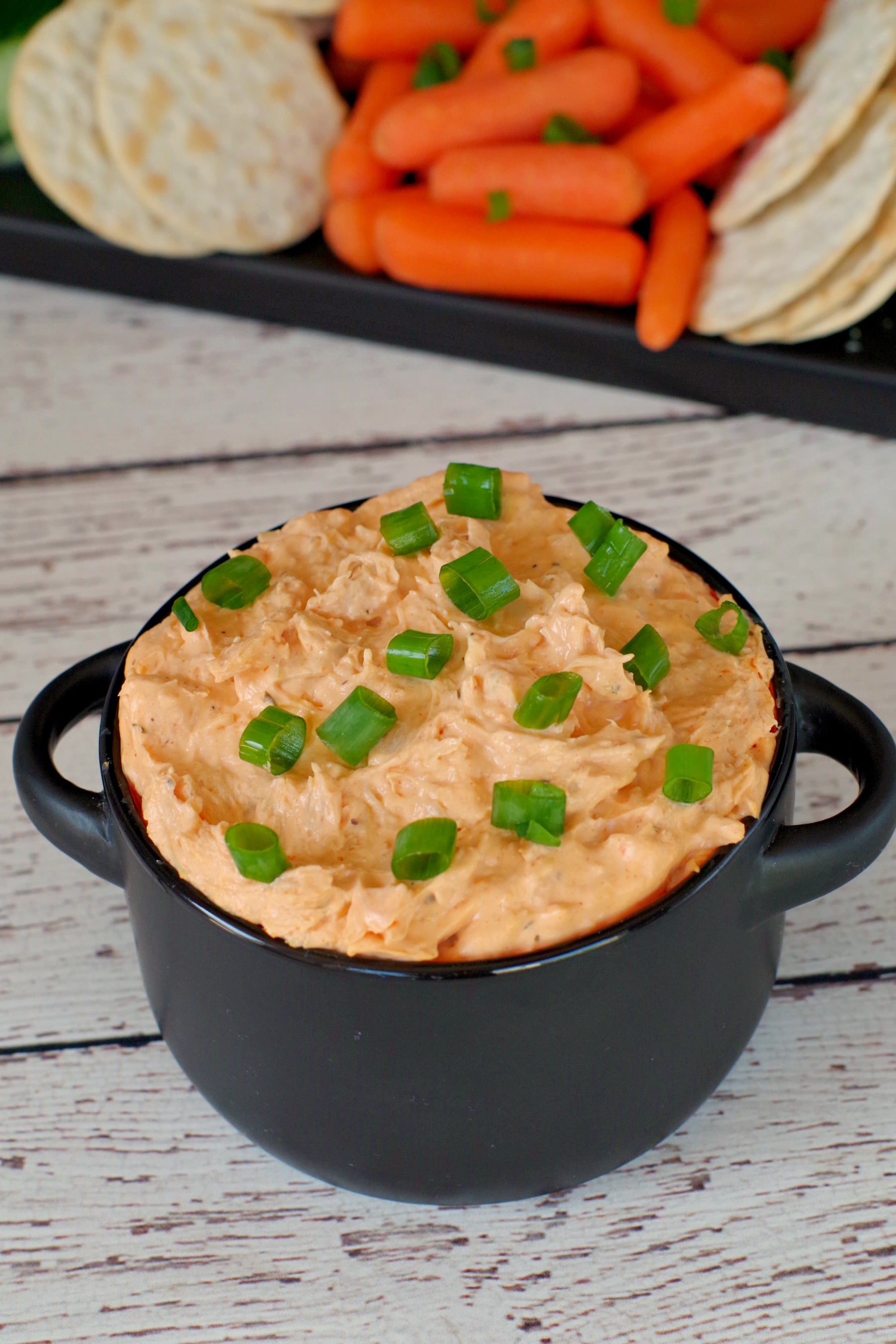 buffalo chicken dip in black container with veggies and crackers in background