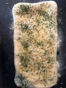 dough brushed with butter and topped with Parmesan mixture