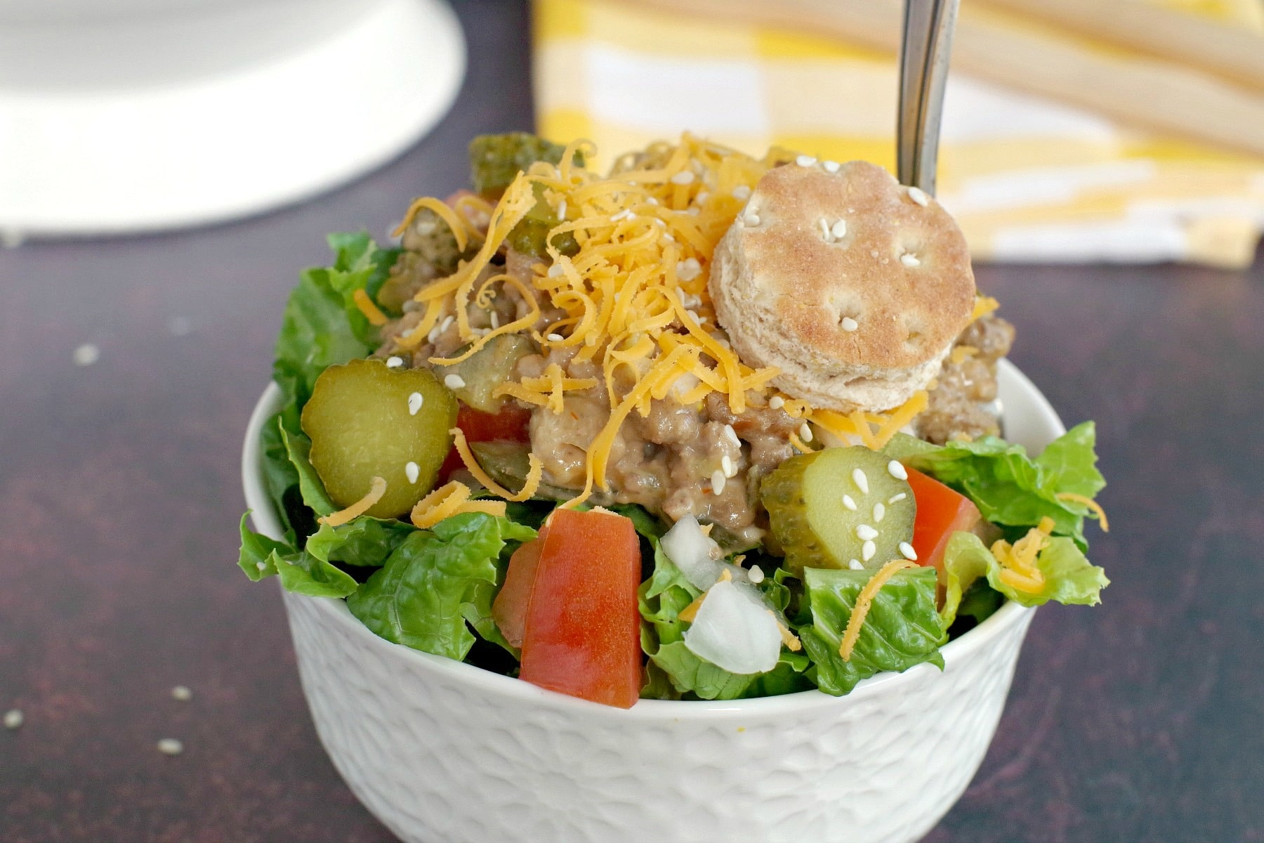 big mac salad in small white bowl, with yellow and white checkered tea towel in background