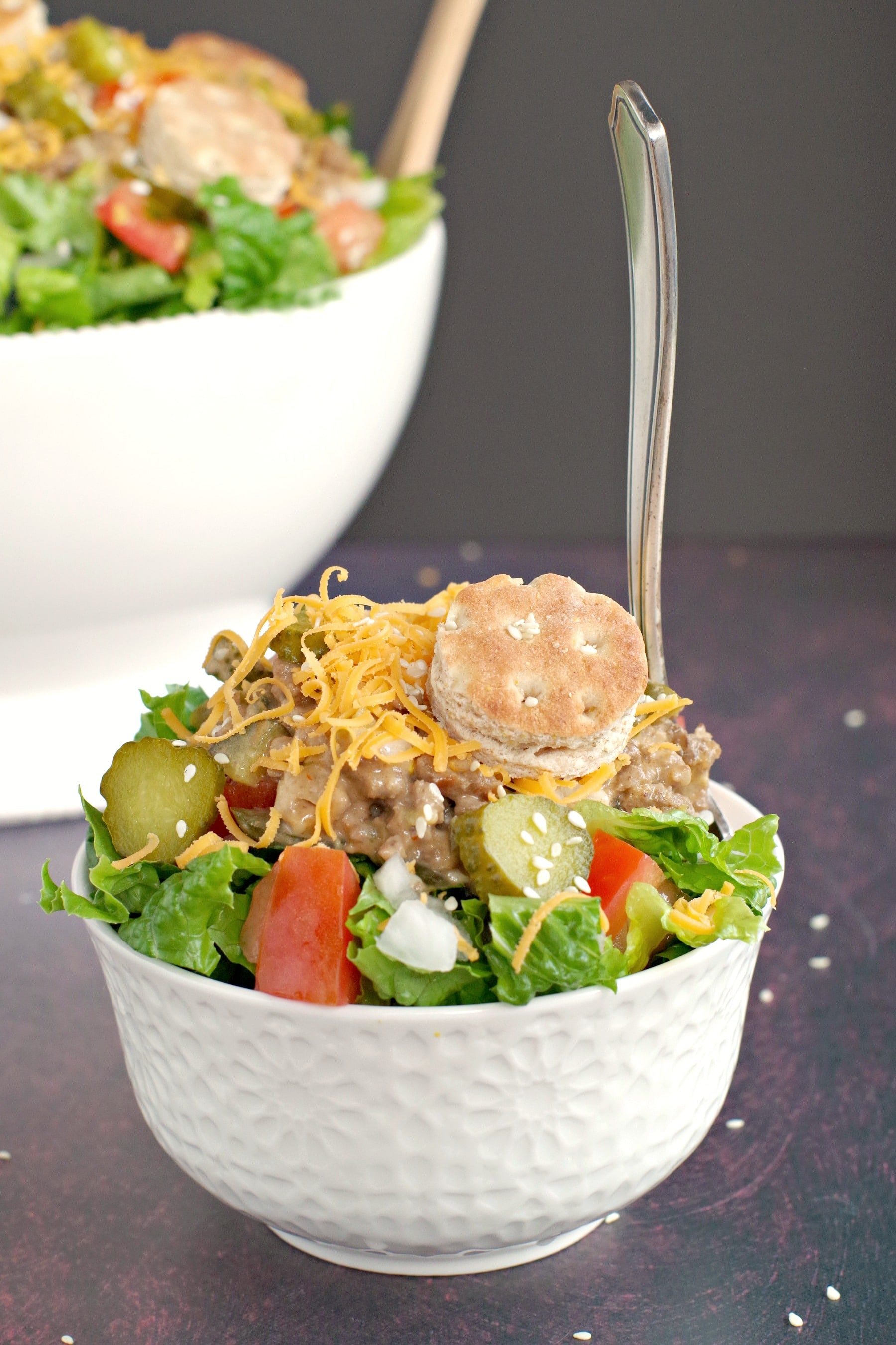 big mac salad in small white bowl with fork in it and large white salad bowl in background