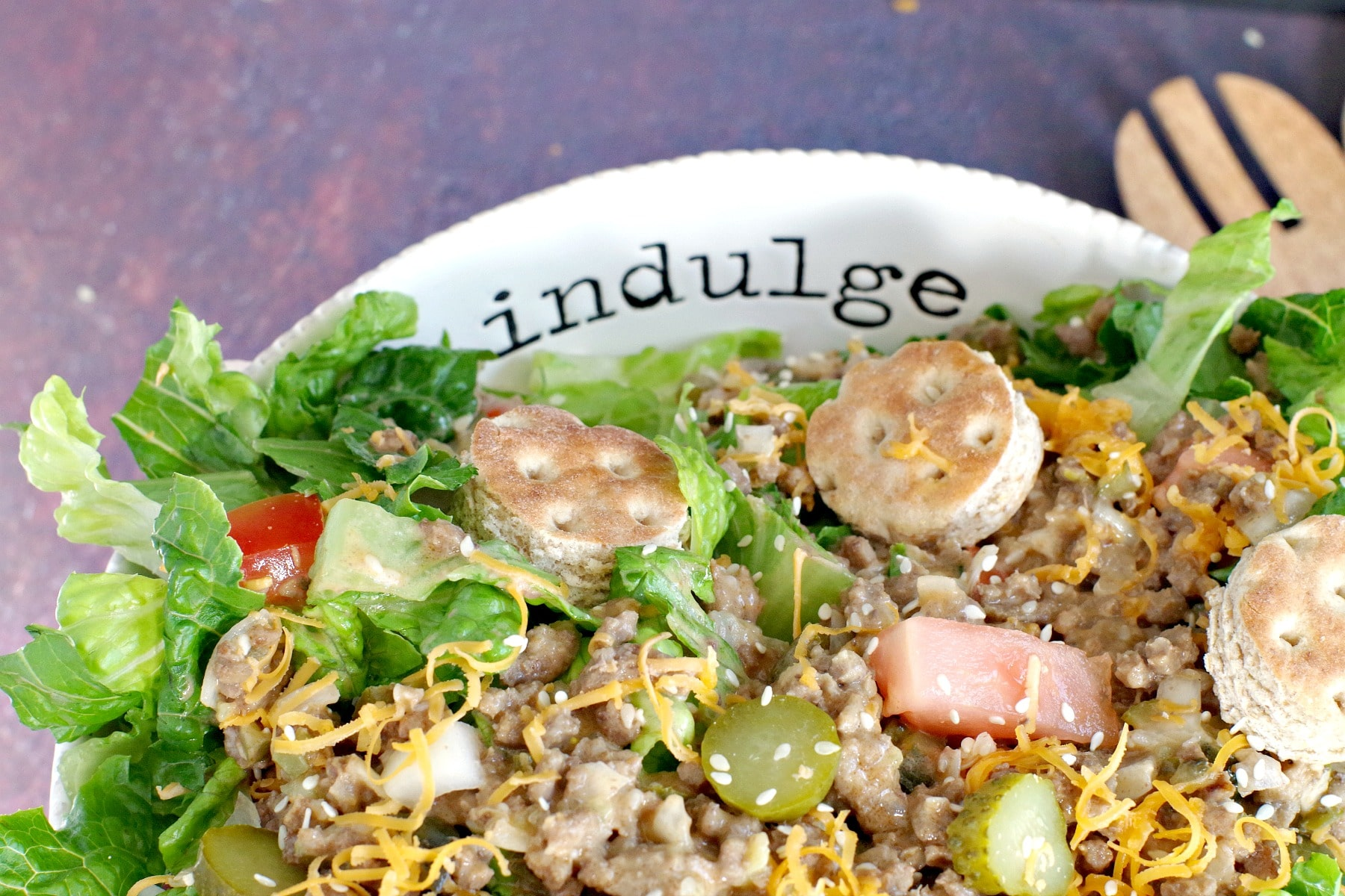 """Big Mac salad (from top) in white bowl) with word """"indulge"""" written on bowl"""