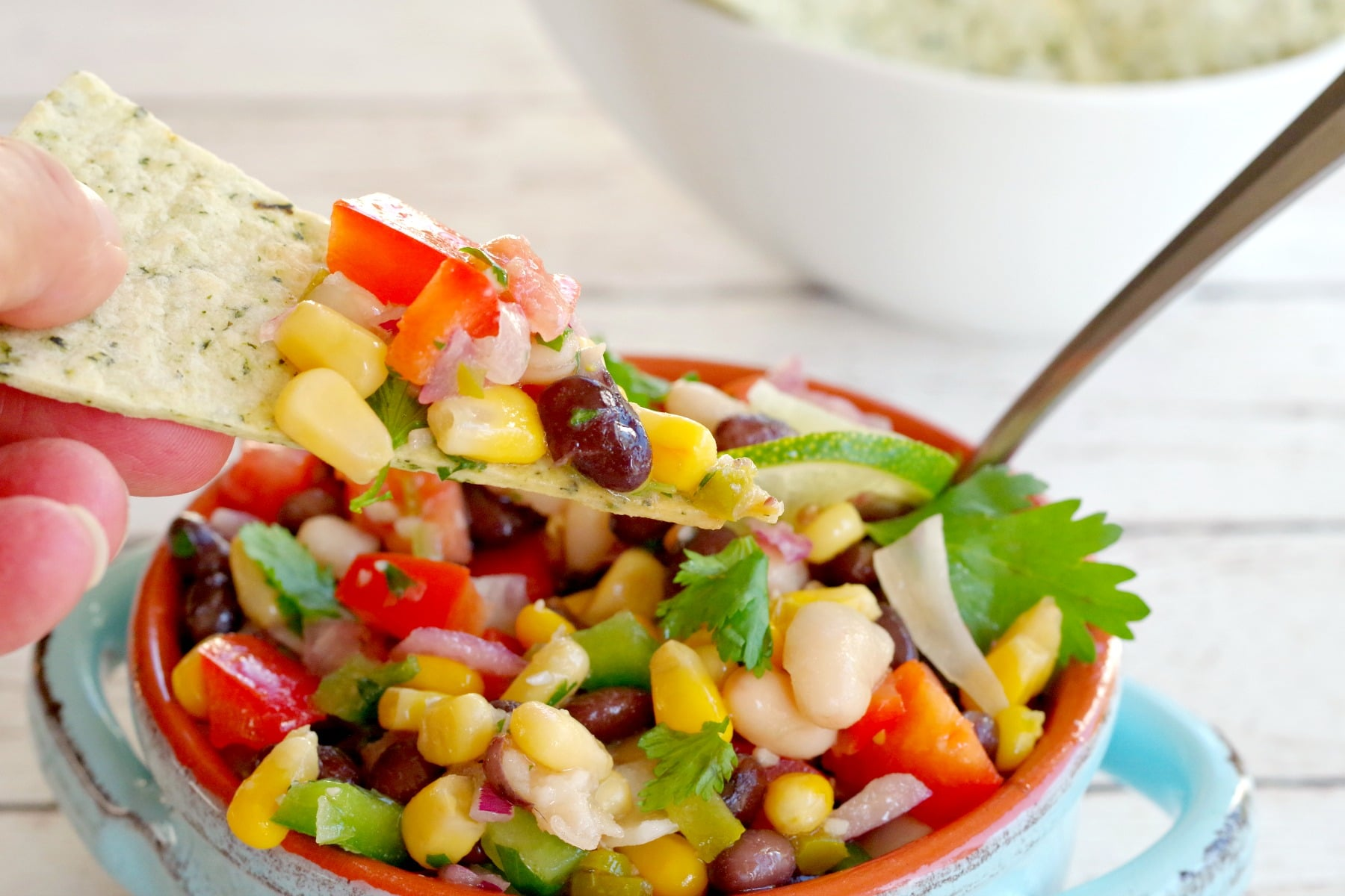 Cowboy Caviar Dip in a bowl with a chip being dipped in
