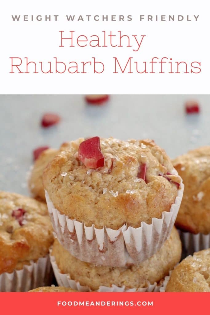 rhubarb muffin stacked on top of other rhubarb muffins with a piece of rhubarb on top