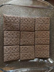 chocolate graham crackers on bottom of glass pan