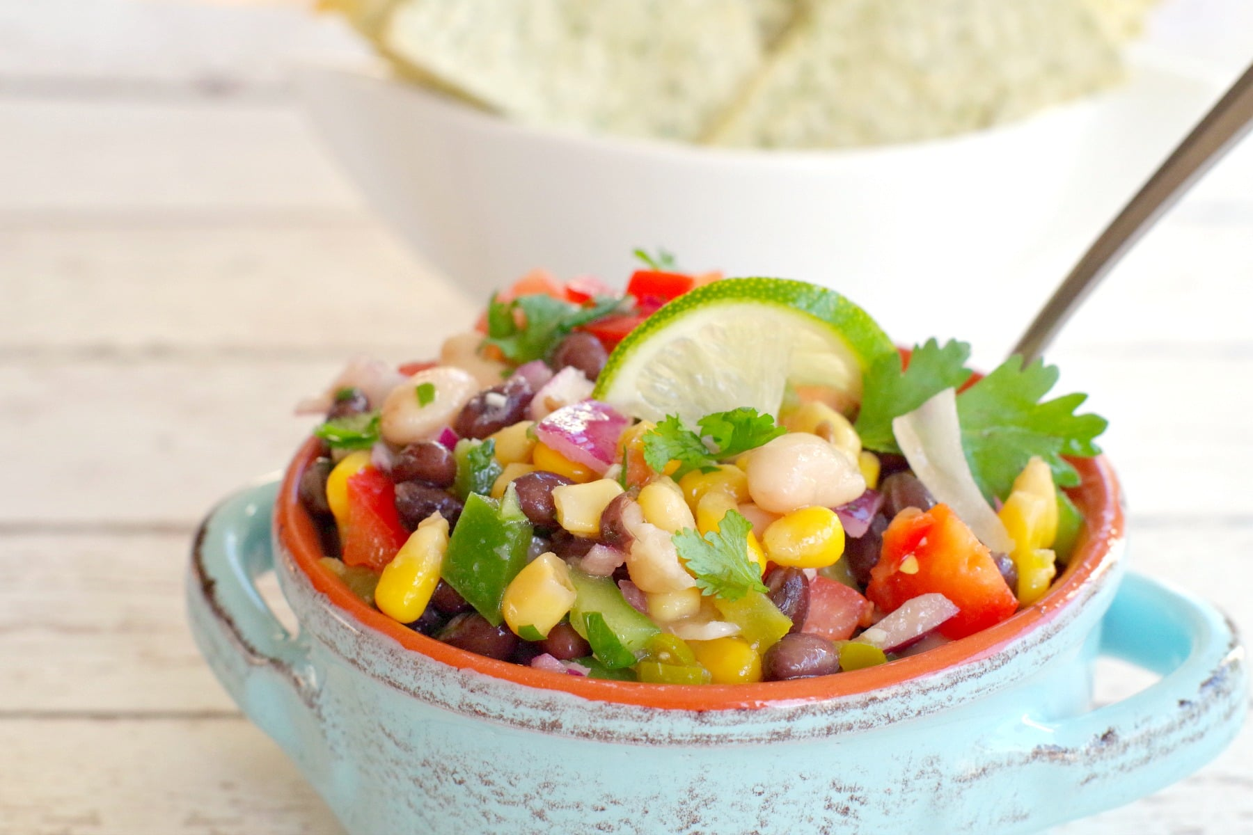 cowboy caviar in a blue bowl with tortilla chips in the background