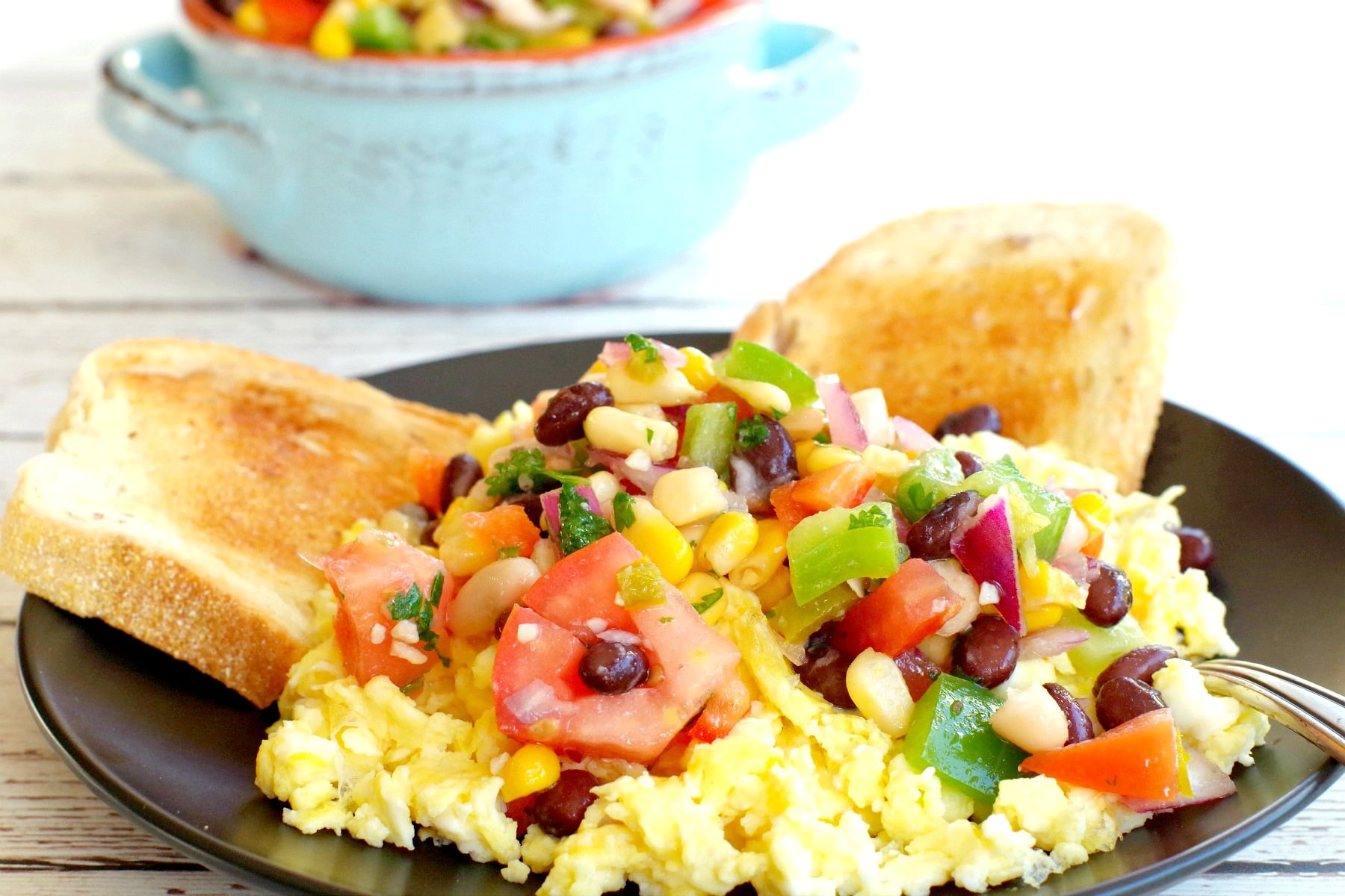 cowboy caviar dip on top of scrambled eggs with toast and dish of dip in the background