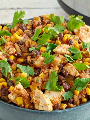 slow cooker mexican chicken in a blue dish with slow cooker in background