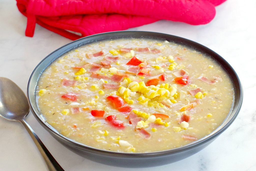 corn chowder in black bowl with red oven mitts in backgroun