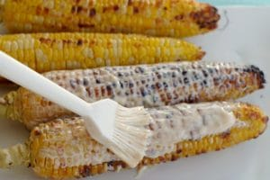 Grilled corn with sauce being spread on it