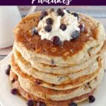 pin with text and photo of a stack of Saskatoon Berry Pancakes with whipped cream and berries on top
