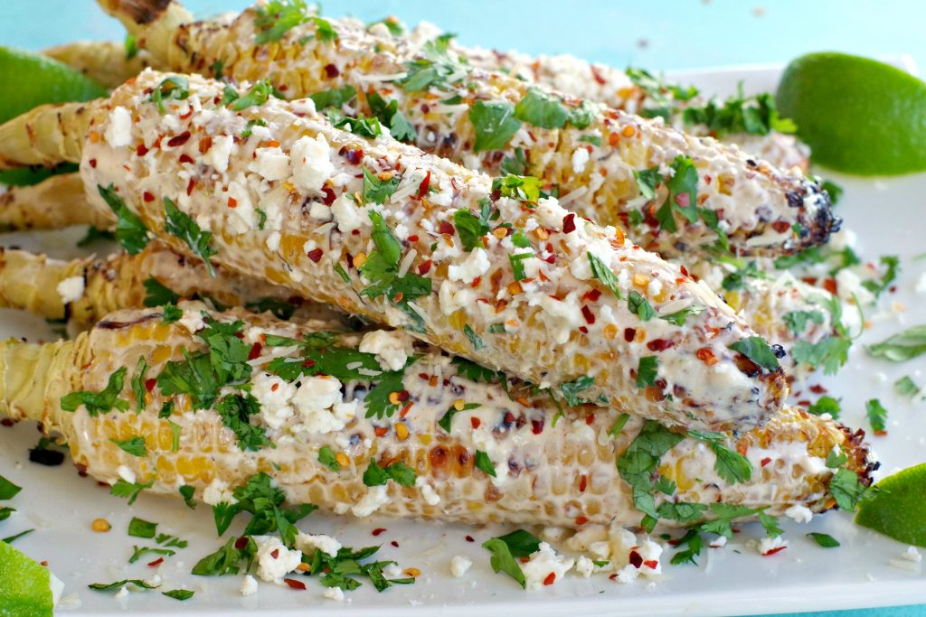 grilled mexican street corn on a white platter