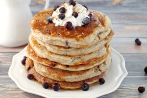 stack of Saskatoon Berry Pancakes with whipped cream and berries on top