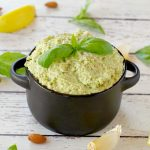 basil pesto with almond in a black dish with almonds, basil, garlic and lemon surrounding the dish