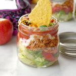 chicken taco salad in a mason jar with more jars, an apple and lunch bag in background