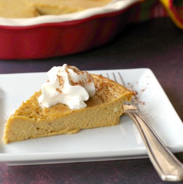 crustless pumpkin pie on a white plate with fork and whole pie in background